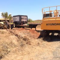 directional drill setup for drilling in solid blue rock with compressor and 14t excavator at the Burrup